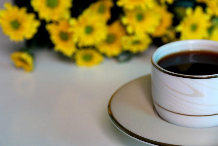 Filiżanka kawy ibukiet żółtych margerytek wtle